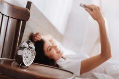 Réveil en forme de coeur argenté avec la femme prenant le selfie derrière Photo libre de droits