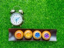 Réveil et bougies parfumées sur la pelouse verte Photos libres de droits