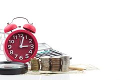 Réveil et calculatrice rouges sur l'euro et le Dolla de billets de banque d'argent Photo stock
