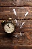 Réveil et deux verres sur le fond en bois Images stock