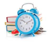 Réveil et fournitures scolaires sur le blanc Image libre de droits