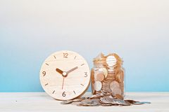 Réveil et pièces de monnaie en bois sur le fond blanc Images stock