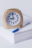 Réveil et stylo sur une pile de papier Photographie stock libre de droits