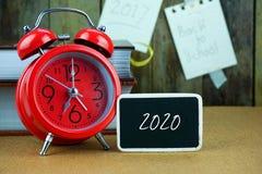 Réveil et tableau noir rouges sur la table en bois Image stock