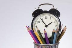 Réveil mis dans le récipient avec les crayons colorés Images stock