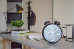 Réveil noir sur la table de travail Image stock