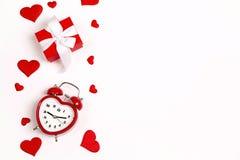 Réveil romantique avec le boîte-cadeau et coeurs décoratifs sur le fond blanc Dessus en bas de la composition images stock