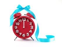 Réveil rouge avec le ruban bleu, minutes avant nouvelle année Images stock