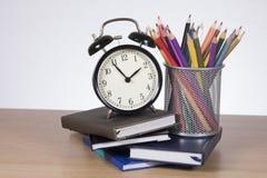 Réveil se tenant sur des livres avec les crayons colorés Photographie stock libre de droits