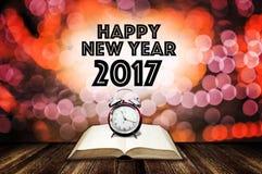 Réveil sur le livre ouvert avec le mot de bonne année Image stock