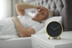 Réveil sur le nightstand avec la femme mûre image libre de droits