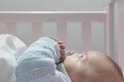Réveillez le bébé garçon de quatre mois se situant dans le berceau avec la tétine image stock