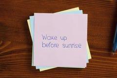 Réveillez-vous avant le lever de soleil écrit sur une note Images libres de droits