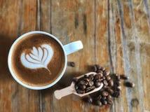 Réveillez-vous avec du café d'art de latte de forme d'amour dans la tasse blanche et les grains de café rôtis dans la cuillère su Images stock