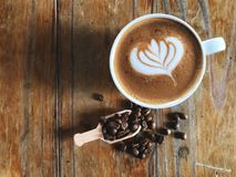 Réveillez-vous avec du café d'art de latte de forme d'amour dans la tasse blanche et les grains de café rôtis dans la cuillère su Photos stock