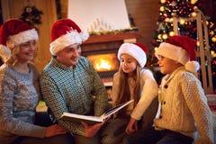 Réveillon de Noël - temps heureux de famille La famille a affiché le livre Image stock