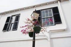 Réverbère avec des pots de fleur sur la façade de maison à Hamilton, Bermudes Fleurs mises en pot sur la colonne d'éclairage avec photographie stock