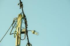 Réverbère classique sur le poteau concret avec des fils de ligne électrique électrique sur la lumière de soirée Image libre de droits