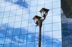 Réverbère de ville contre un mur de verre Photos stock