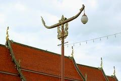 Réverbère formé thaïlandais de bateau d'emballage de cru contre le toit carrelé du temple et le ciel nuageux, endroit historique  images stock