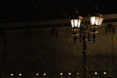Réverbère léger pendant une tempête de neige photographie stock libre de droits