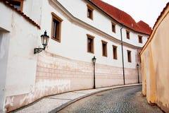 Réverbères sur une route incurvée avec de vieux pavés ronds et maisons blanches Photographie stock libre de droits