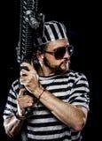Révolte, concept d'émeute de prison. Homme tenant une mitrailleuse, prisonnier Image stock