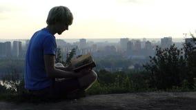 Rêvant l'homme lit un livre sur la plate-forme d'observation dans Kyiv dans le ralenti banque de vidéos