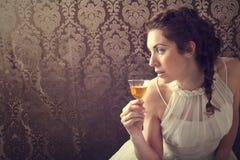 Rêvant la femme boit un verre d'excellent whisky écossais photos stock