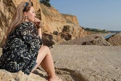 Rêver la belle fille s'asseyant sur de grandes pierres Image stock