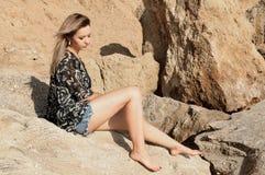 Rêver la belle fille s'asseyant sur de grandes pierres Images stock