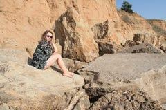 Rêver la belle fille s'asseyant sur de grandes pierres Photographie stock libre de droits