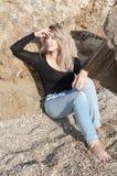 Rêver la belle fille s'asseyant sur de grandes pierres Photos stock