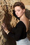 Rêver la belle fille s'asseyant sur de grandes pierres Photos libres de droits