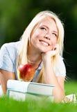 Rêver la femme se trouvant sur l'herbe près de la pile des livres Photo stock
