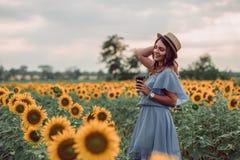 Rêver la jeune femme dans la robe bleue et le chapeau tenant une tasse de café dans un domaine des tournesols à l'été, vue de son images libres de droits