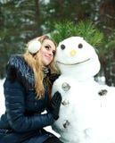 Rêver la jolie fille avec le bonhomme de neige Photo stock