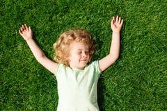 Rêver la petite fille adorable se trouvant sur l'herbe photographie stock libre de droits