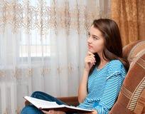 Rêves de jeune fille au-dessus de livre Image stock