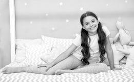 Rêves doux de souhait L'enfant de fille s'asseyent sur le lit dans sa chambre à coucher L'enfant disposent à aller au lit Temps a image stock