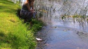Rêveusement la fille a laissé le bateau de papier de bateau d'origami flotter sur l'eau de rivière clips vidéos