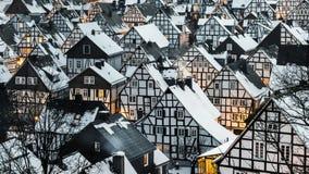 Rêveusement la neige a couvert le village d'hiver photos libres de droits