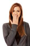 Ríe nerviosamente la mujer adolescente que cubre su boca con la mano Imagen de archivo libre de regalías