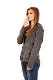 Ríe nerviosamente la mujer adolescente que cubre su boca con la mano Foto de archivo