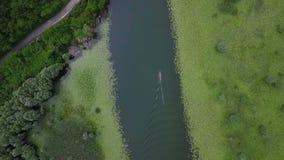 Río aéreo del tiroteo con los lirios y el barco en fluir superficial del agua alrededor de la colina almacen de video