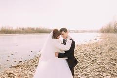 Río aseado cara a cara feliz del abarcamiento de los pares de la boda, de novia y del novio Foto de archivo libre de regalías