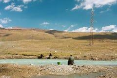 Río azul del color con algunos pescadores en un valle de la montaña debajo del cielo nublado Foto de archivo