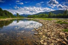 Río claro con las ventajas de las rocas hacia las montañas Imágenes de archivo libres de regalías