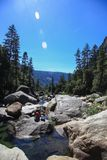 Río con el hombre de la pesca en bosque en el parque nacional de Yosemite fotografía de archivo