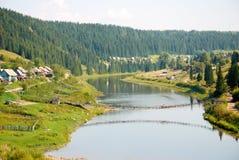 Río con el puente de suspensión en Urales, Rusia Imágenes de archivo libres de regalías